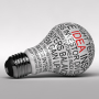 Single light bulb on white background with business expressions on it highlighting the word idea
