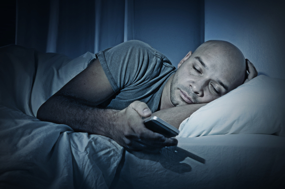 Young Cell Phone Addict Man Sleeping At Night In Bed While Using